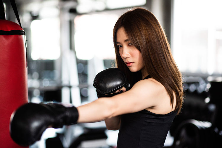 Confident young woman practicing boxing in gym
