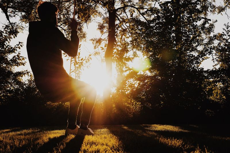 The Great Outdoors - 2018 EyeEm Awards Beauty In Nature Beautiful Sunlight Sunset Holiday Silhouette Nature Photography Silhouette Real People One Person Sunlight Lifestyles Tree Leisure Activity Plant Nature Full Length Low Angle View Men Lens Flare Sky Outdoors Growth Land Sunbeam
