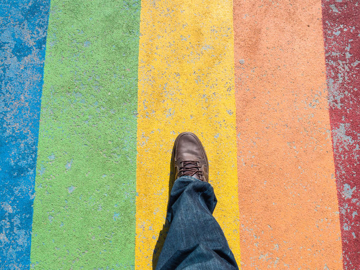 Low section of man walking on multi colored footpath