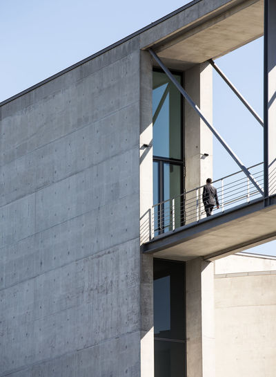 Low Angle View Of Man Standing On Elevated Walkway Amidst Building