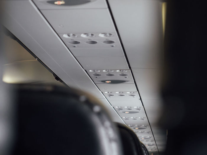 Low angle view of lighting equipment on ceiling in airplane