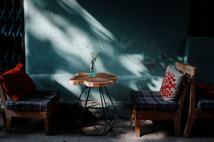 Empty chairs and table against wall at sidewalk cafe