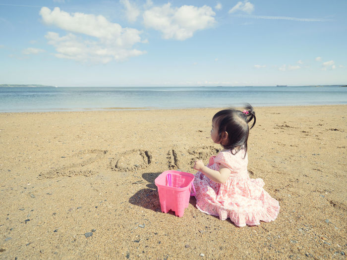 Side view of girl sitting on shore at beach against sky