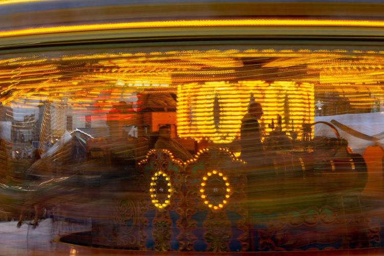 Motion blur merry go round ride at the Christmas Fair, Bury St Edmunds, Suffolk, UK Christmas Fayre Christmas Fair Fairground Ride Fairground Attraction Fairground Lights Motion Blurred Motion Speed Illuminated Amusement Park Ride Slow Shutter Merry Go Round Lights Street Entertainement