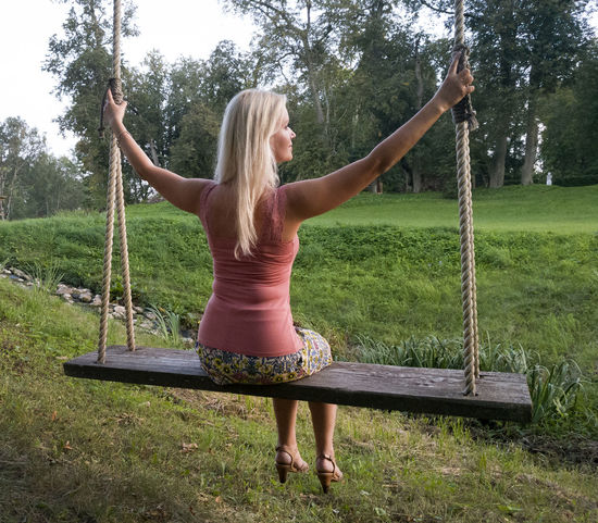 Blond hair woman sitting on swing in park, Estonia. Adult Beauty In Nature Blond Hair Casual Clothing Day Full Length Grass Leisure Activity Lifestyles Nature One Person Outdoors Park - Man Made Space People Real People Rope Swing Swing Tree Water Young Adult Young Women