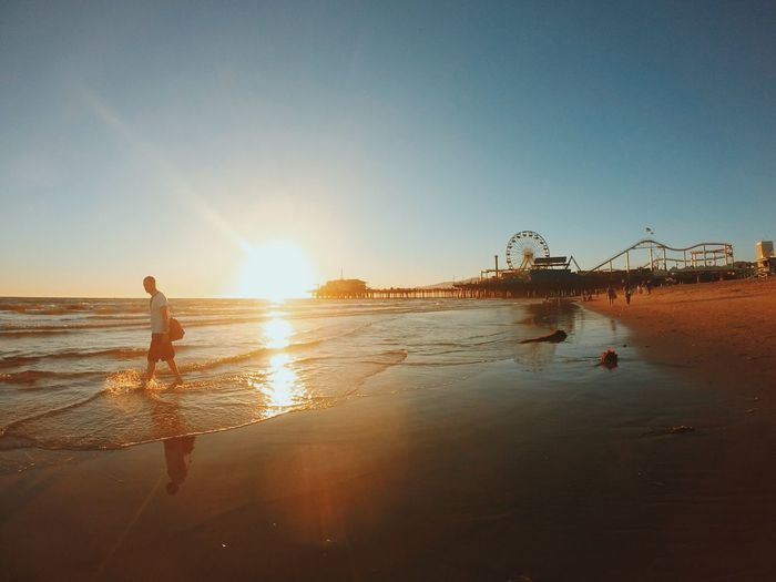 Man Walking On Beach By Santa Monica Pier Against Clear Sky During Sunset