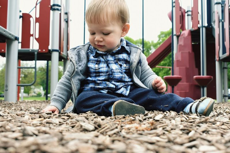 Baby boy playing with wood chips at playground