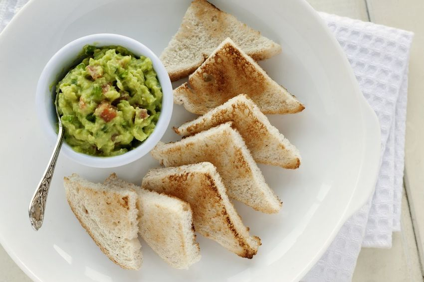 Guacamole bowl with bread toast appetizer. Food And Drink High Angle View Healthy Eating No People Freshness UnykaProductions Guacamole Porcelain Bowl Studio Photography Appetizer Snack DIP Natural Light Mexican Food Spread Bread Toast Avocado Red Peppers Green Peppers Onion Tomato White Background Texmex Bowl Ready-to-eat Food Stories