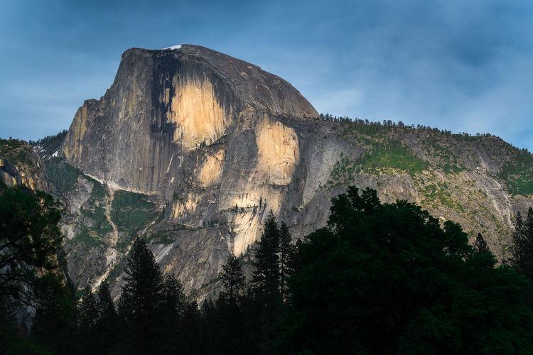Low angle view of sun shining through rocks