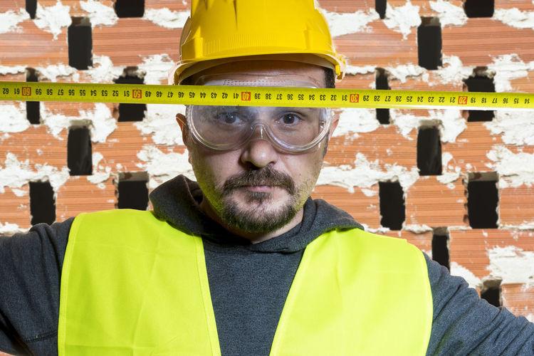 Portrait of confident architect with tape measure at construction site