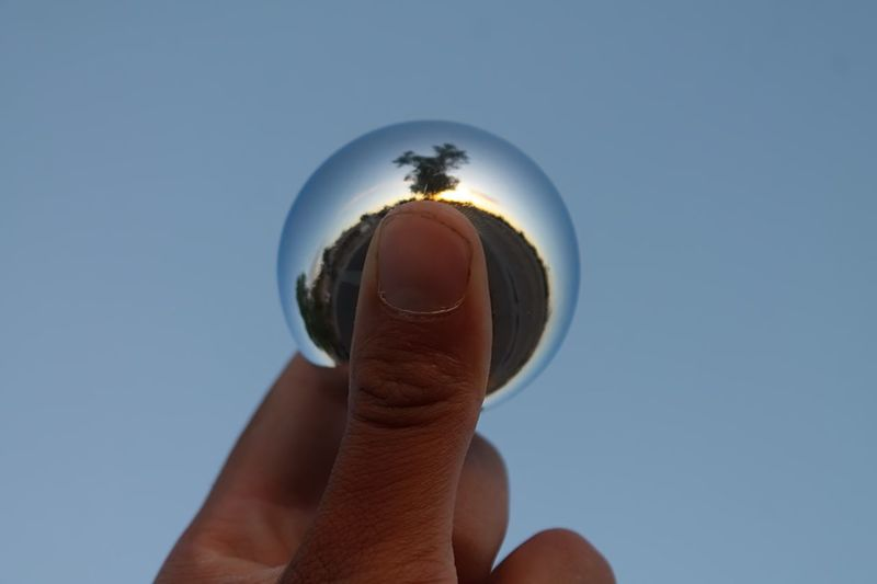 Cropped image of man holding crystal ball against sky