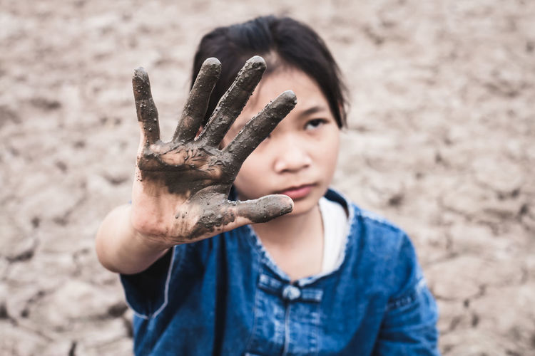 Girl with muddy hand on drought field