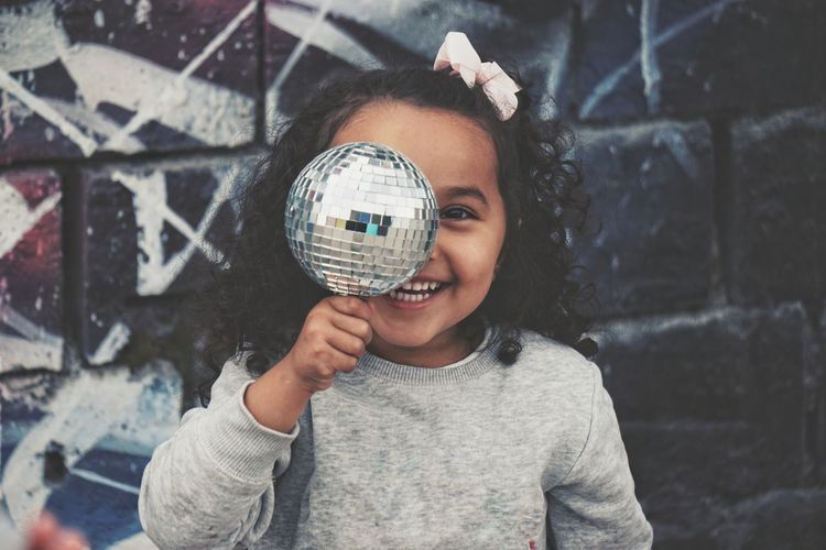 Portrait of smiling girl holding disco ball against wall