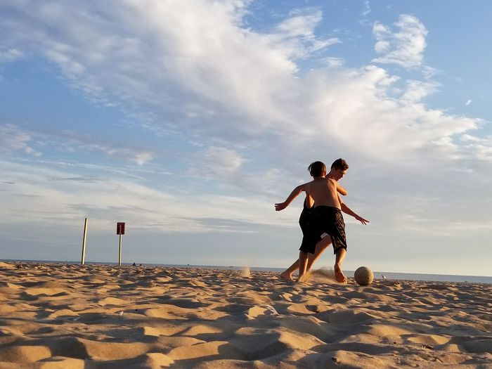 Full length of men jumping on beach against sky