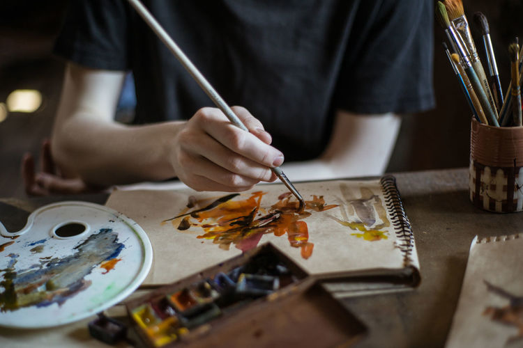 Art Arts Culture And Entertainment Art And Craft ArtWork Artist Paint Painting Painting Art One Person Creativity Skill  Brush Craft Paintbrush Hand Table Human Hand Real People Occupation Human Body Part Watercolor Paints Workshop Midsection Workbench