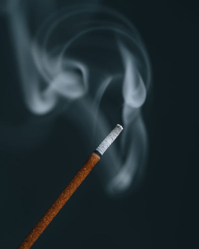 Close-up of cigarette smoking against black background
