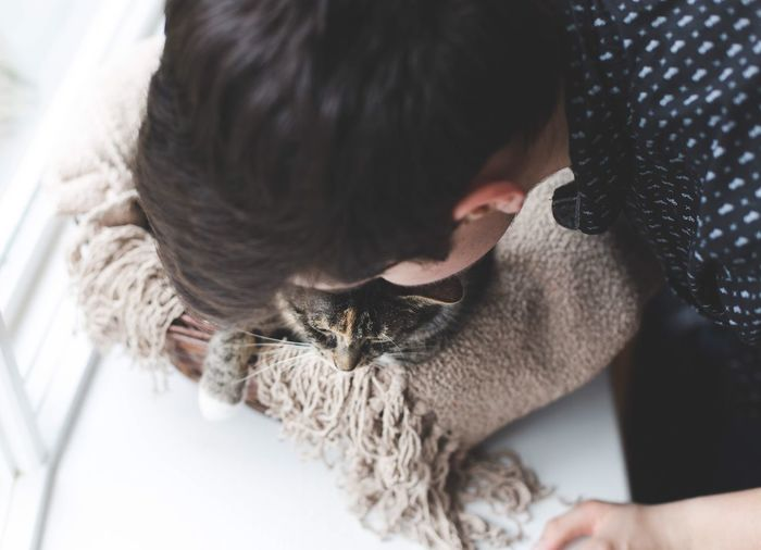 High angle view of teenage boy with cat at home