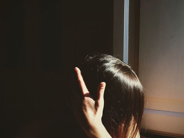 Close-Up Of Woman With Obscured Face Against Wall
