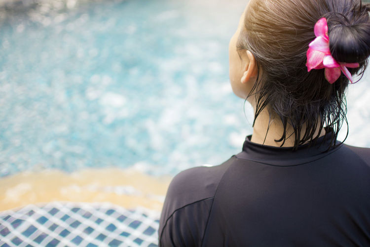 Rear view of woman in swimming pool against sea