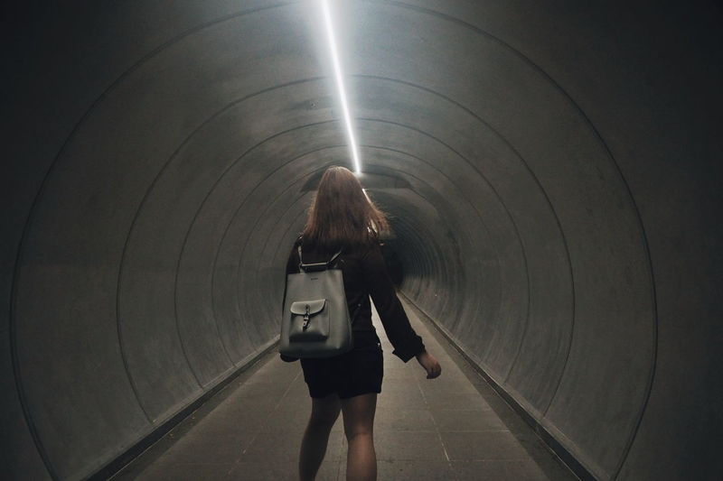 Rear View Of Woman Standing In Tunnel