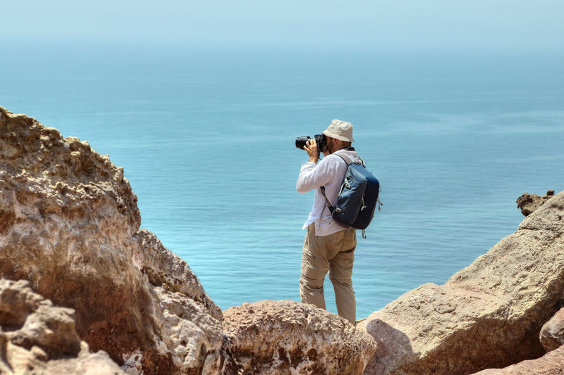 Photographer traveler in a panama on his head, and a backpack behind his shoulders stands on the edge of a cliff over the sea, Hormuz Island, Hormozgan Province, southern Iran. Hormuz Island Hormozgan Province Hormozgan Province Iran Iran Iranian People Tourist Traveler Tourism Backpacker Photographer Man Mountains Rock Rocks Taking Photos Taking Pictures Camera Sea Water Persian Gulf.
