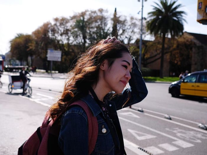 Young woman looking away while walking on road in city