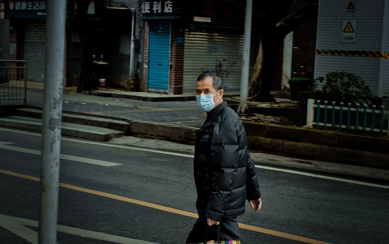 Full length of man standing on road in city