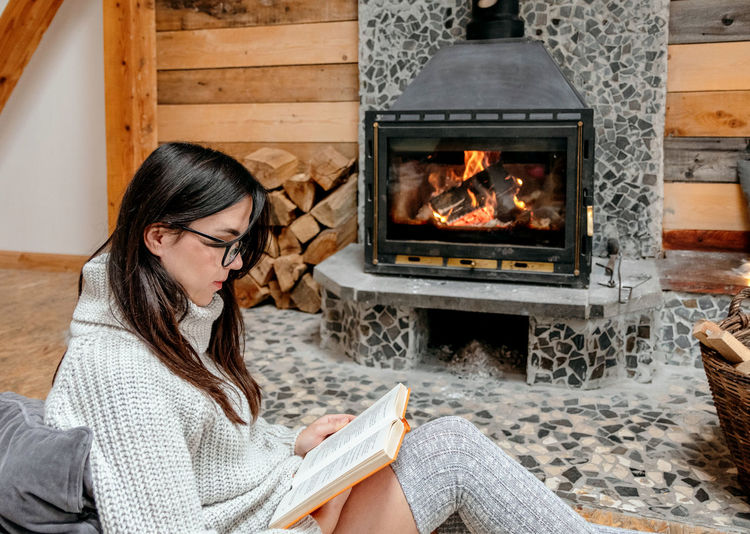 Young woman sitting by fireplace in cozy cabin, reading a book.