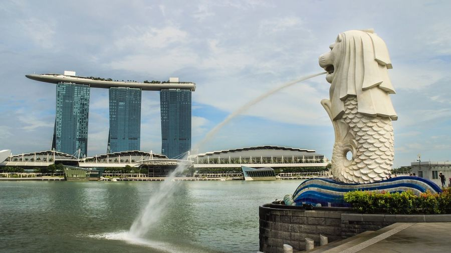 View of merlion statue and marina bay against sky