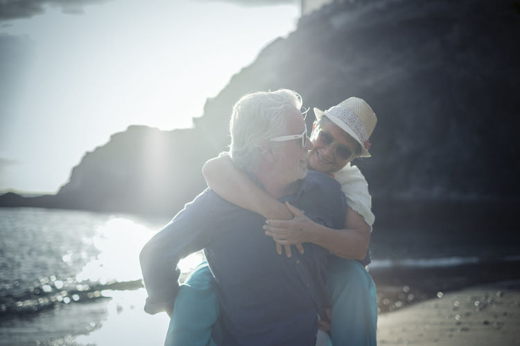 Senior man giving piggy back ride to woman at beach