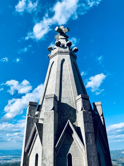Low angle view of statue by building against sky