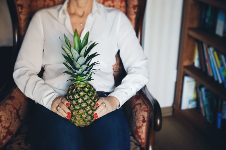 Midsection of woman holding pineapple at home