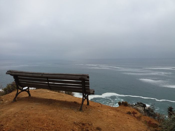 Empty Bench On Cliff By Sea Against Sky