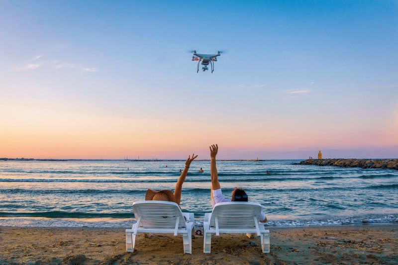 Rear view of people photographing sea at sunset
