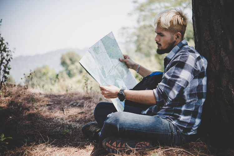Side View Of Young Man Reading Map While Sitting On Field