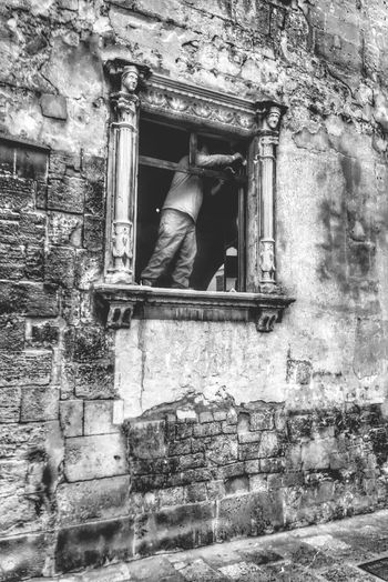 a Worker Renovating an Old Building . Black & White photo