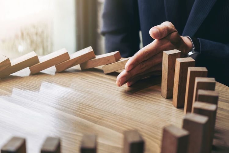 Entrepreneur Planning Businessman Close-up Day Finance Human Body Part Human Hand Indoors  Investment Marketing Men Occupation One Person People Playing Protection Real People Selective Focus Stop Strategy Wood - Material Wood Game Wooden Block Working