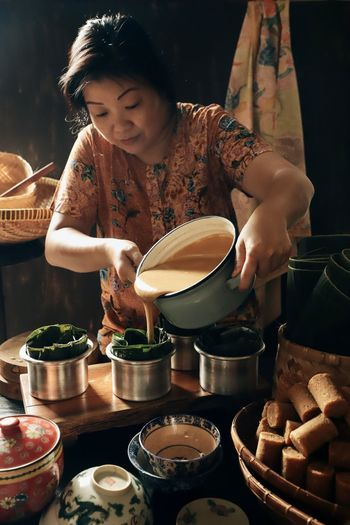 A peranakan lady is making nian gao for lunar new year