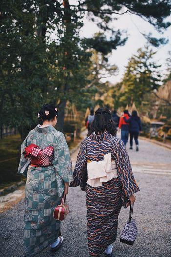 Rear view of woman wearing kimono walking on road