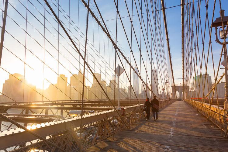 Man on footbridge against sky