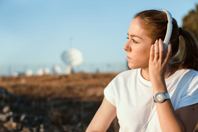 Young woman wearing headphones against sky
