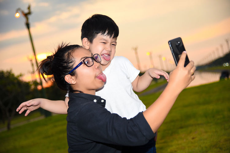 Playful mother and son sticking out tongues while taking selfie with smart phone on field during sunset