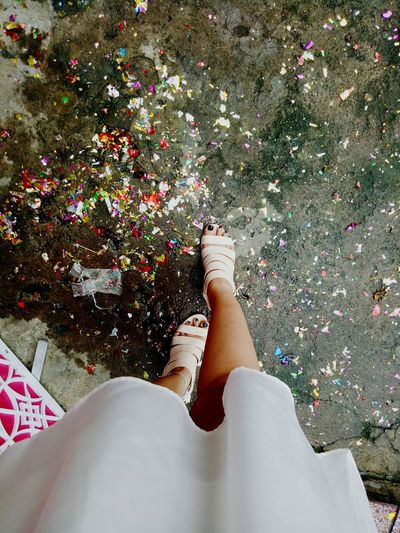Low section of woman standing by confetti on footpath