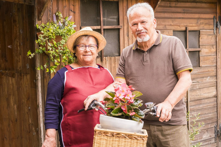 Portrait Of Senior Couple Standing With Potted Plant In Bicycle Basket Against House