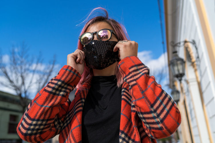 Portrait of young woman wearing sunglasses against sky during winter
