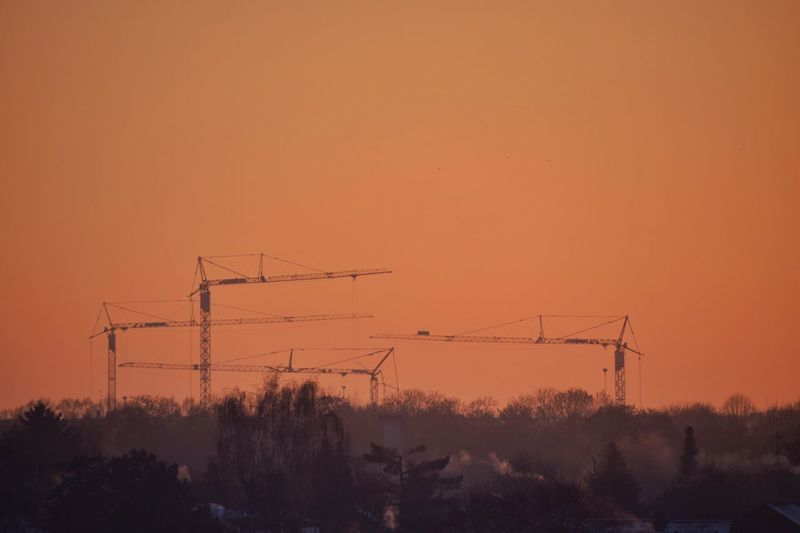 Silhouette of cranes against sky during sunset
