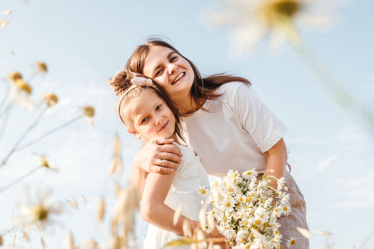 Portrait of mother and daughter by plants against sky