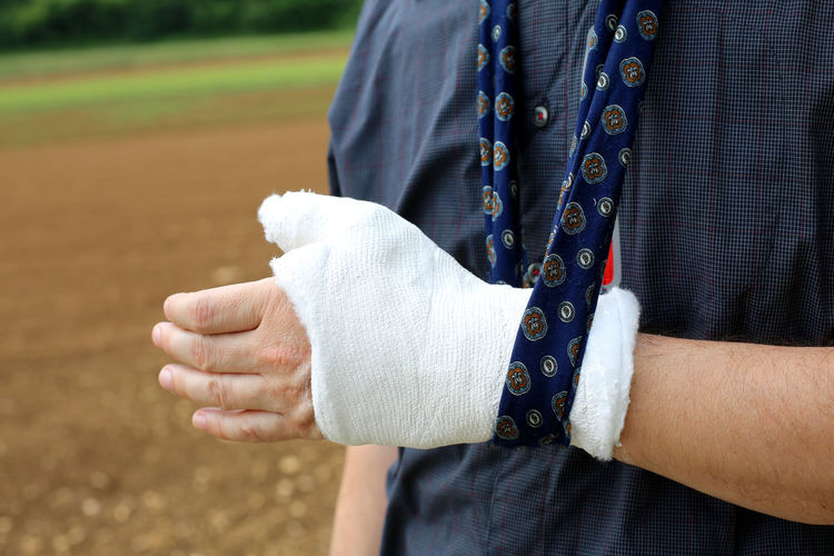 Midsection of man wearing bandage on injured hand while standing on land