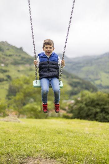 Portrait of boy swinging in playground