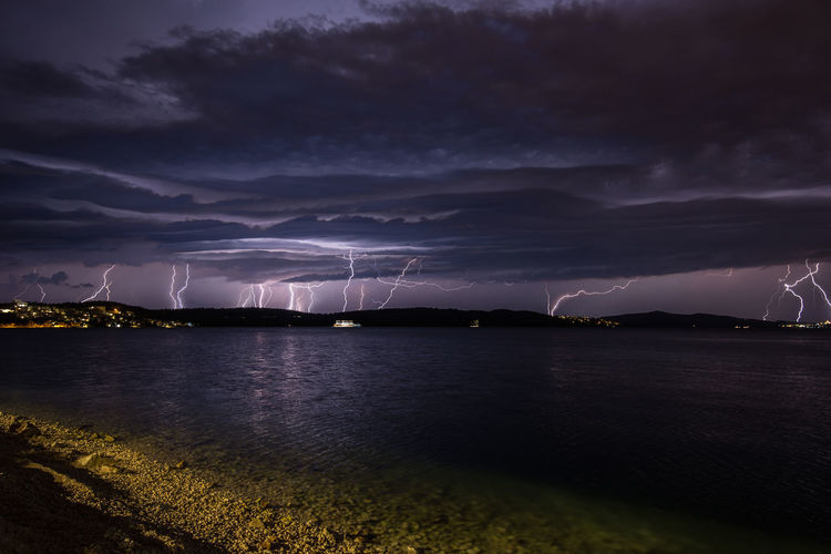 Lightning In Cloudy Sky Over Sea At Night